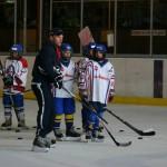 Coach en spelers op de Ijshockeybaan
